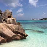 Blick auf Steine und türkisfarbenes Meer - das sind die Seychellen